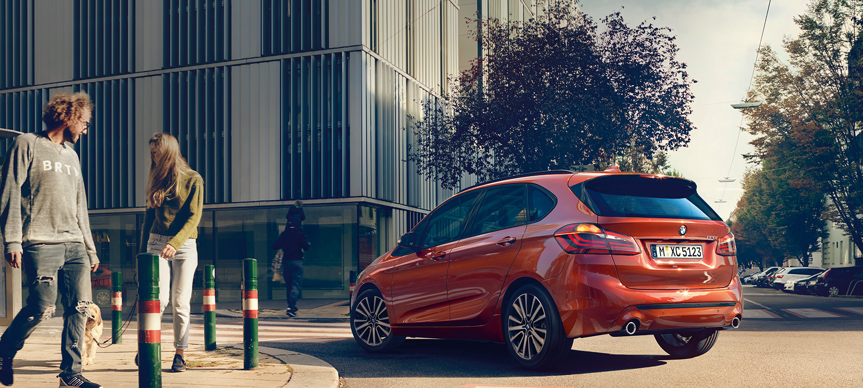 BMW 2 Series Active Tourer 220i F45 Facelift 2018 Sunset Orange metallic three-quarter rear view driving on the road